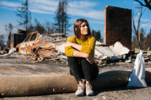 photo of woman sitting in front of destroyed home feeling despair ID 122117345 © Vlad Teodor | Dreamstime.com